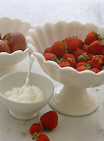 Fresh strawberries in a white bowl with a scalloped edge is accompanied by a bowl of cream