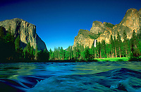 A river running through Yosemite Valley in Yosemite National Park, California. The river run past rocky peaks, forest and a waterfall beneath a blue sky.<br />