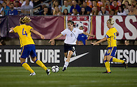 Heather O'Reilly (9) of the USWNT crosses the ball between Nilla Fischer (18) and Linda Sembrant (4) of Sweden at Rentschler Field in East Hartford, Connecticut.  The USWNT defeated Sweden, 3-0.