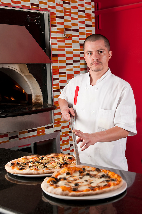 Young hispanic cook getting pizza into a restaurant counter.