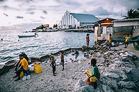 People on the shore in an area beside the sea that  many children use to wash in. Most of the island's houses do not have running water and locals usually have bucket showers or bathe in the polluted sea water.