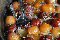 A tub of sweet gulab jamun and two metal spoons at the Shimla bazaar.