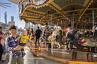 Jane's Carousel in Brooklyn Bridge Park in the Brooklyn neighborhood of Dumbo during the annual Art Under the Bridge Dumbo Arts Festival on Saturday, September 28, 2013.  Dumbo has been a neighborhood shared by industry and artists but high real estate prices have created opportunities for development with the subsequent increase in rents.  (© Richard B. Levine)