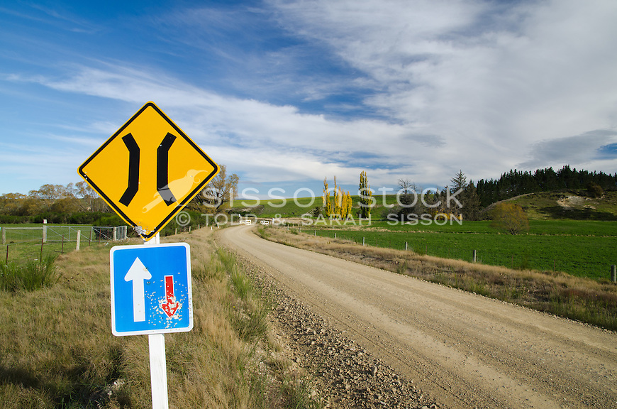 Road sign with bullet holes on gravel dirt road in central Otago New Zealand.  Fence and bridge in background. Autumn.