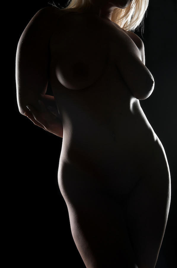 Youn caucasian woman posing nude in dim light.
