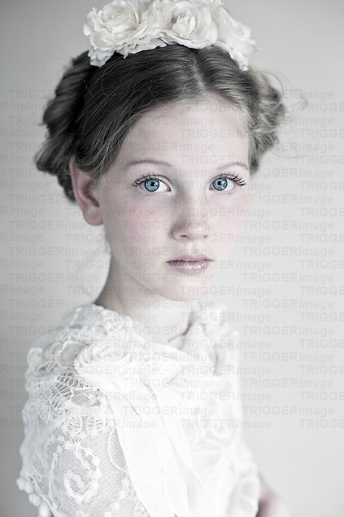 Headshot of young girl with  clear blue eyes wearing white lace with roses in her hair looking at camera