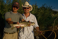 Anglers pose with a large rainbow trout (Oncorhynchus mykiss) caught while fly fishing the Blackfoot River near Missoula Montana.