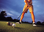 A low angle shot of a golfer preparing to tee off at a golf course
