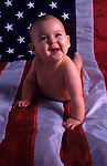 Baby (6 months old) lying on an American Flag smiling