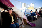 RENO, NV - OCTOBER 6:  Tammy Tyra of Texas tries to warm up in a tent city for the homeless in downtown Reno, Nevada October 6, 2008. Tyra works cleaning trucks, but is unable to make enough money to afford housing. The City of Reno set up the tent city when existing shelters became overcrowded as Nevada struggles with one of the highest unemployment rates in the country. (Photo by Max Whittaker/Getty Images)