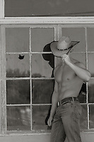 sexy shirtless young cowboy leaning against a building in New Mexico