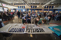 """NWA Democrat-Gazette/J.T. WAMPLER Students sign a banner Monday Feb. 13, 2017 at Rogers Heritage High School. The banner reads: """"Heritage United: We are one, divided by none."""" Students were encouraged to sign their name and add a message on what unites them as opposed to what divides them."""