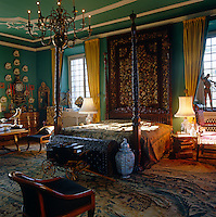 A tapestry hangs above the large carved four-poster bed in this impressive green and white bedroom