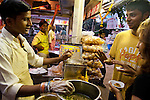 Visitors to chowpati beach enjoy Pani Puri, a favorite street food snack. Mumbai, August 2009