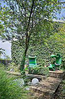 Two green chairs are set on a decked terrace area in a garden shaded by a tree.