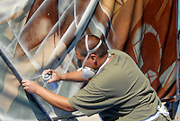 Jessie Castillo, 23, paints during the 6th Annual Pico Festival and Classic Car Show at Virginia Avenue Park on Sunday, October 2, 2011