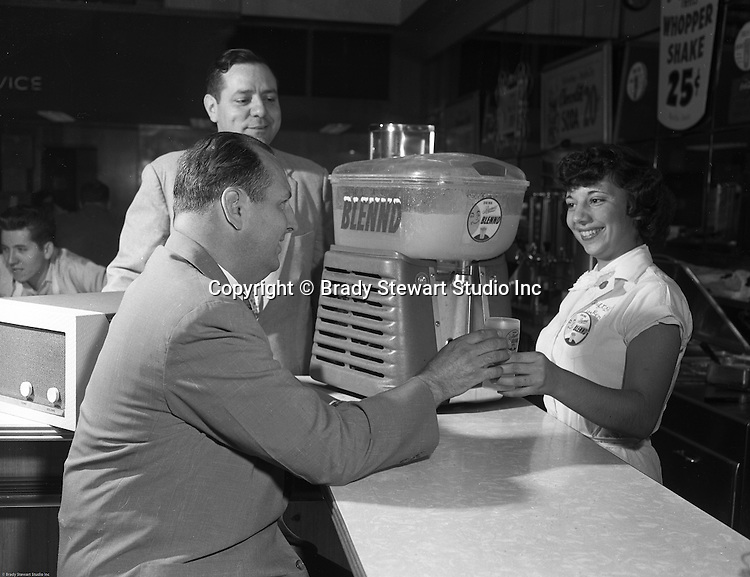Pittsburgh PA:  A Thrift Drug waitress serving Lester Hamburg of Hamburg Brothers, a Lemon Blennd.  Hamburg Brothers had a weekly radio contest that gave away a phonograph and this waitress won the phonograph.<br />