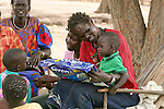 In Rumbek, South Sudan, a mother speaks to the children about preventing malaria by sleeping under long lasting insecticide-treated mosquito nets, such as Serena, distributed by the international NGO, Population Services International (PSI).
