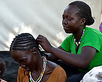 A woman braids the hair of another woman in the Gendrassa refugee camp in South Sudan's Upper Nile State. More than 110,000 refugees were living in four camps in Maban County in October 2012, but officials expected more would arrive once the rainy season ended and people could cross rivers that block the routes from Sudan's Blue Nile area, where Sudanese military has been bombing civilian populations as part of its response to a local insurgency. Conditions in the camps are often grim, with outbreaks of diseases such as Hepatitis E.