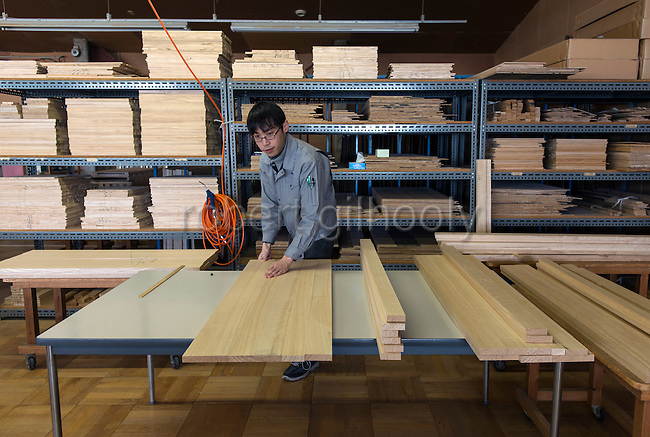 A craftsman aligns the lengths of kiri wood in preparation for laminating at  Kamo Kiri-tansu maker Asakura Kagu in Niigata City, Niigata Prefecture Japan on Feb. 21, 2017. ROB GILHOOLY PHOTO
