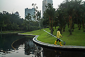 A cleaner walks along a pond at the KLCC park in Kuala Lumpur, Malaysia.