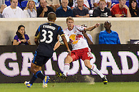 Markus Holgersson (5) of the New York Red Bulls crosses the ball as Fabio Alves (Fabinho) (33) of the Philadelphia Union defends. The New York Red Bulls and the Philadelphia Union played to a 0-0 tie during a Major League Soccer (MLS) match at Red Bull Arena in Harrison, NJ, on August 17, 2013.