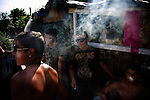 Stojan, center, and friends smoke cigarettes in the shade on the hottest day of the year during the celebration for a baptism in the Nova Gazela camp.