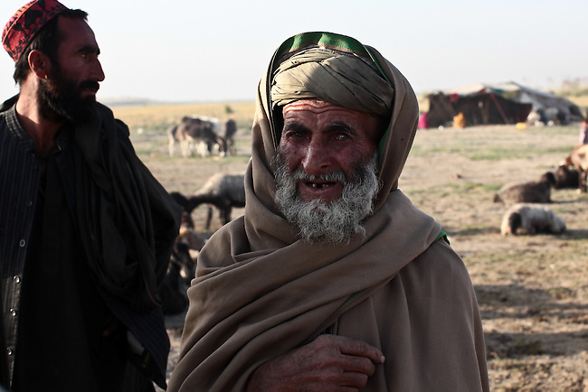 An old man from the nomadic Kuchi tribe meets with U.S. soldiers from Company D, 1st Battalion, 22nd Infantry Regiment on patrol in Malajat, near Kandahar, Afghanistan. Oct. 9, 2010. DREW BROWN/STARS AND STRIPES