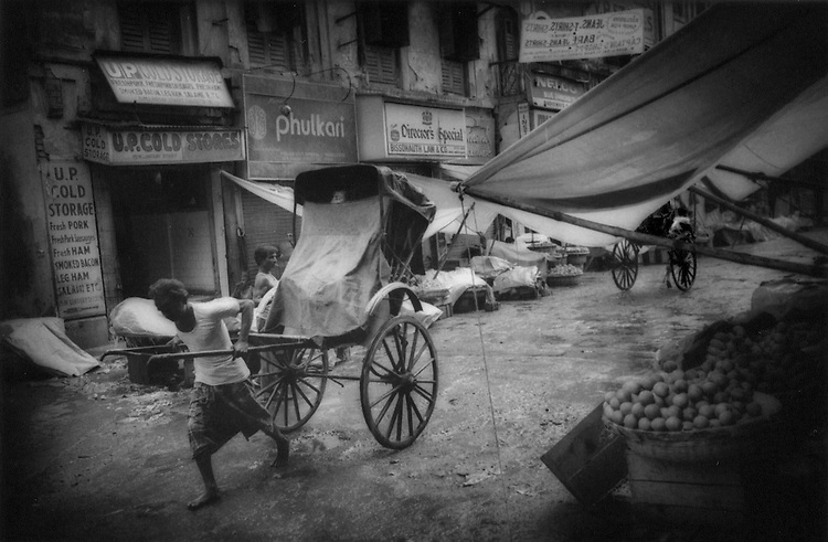On the way home a monsoonal shower: A rickshaw wallah pulls passenger while he is peeking out of covering, Calcutta, India.