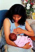 Woman breast feeds her newborn