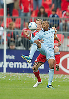 Sporting KC forward Teal Bunbury #9 and Toronto FC defender Ty Harden #20 in action during an MLS game between Sporting Kansas City and the Toronto FC at BMO Field in Toronto on June 4, 2011...