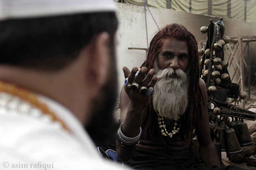 bari imam shrine, islambad, pakistan 2004: a sadhu or holy man is visited by a devotee of the bari imam seeking advice on life and matters of the heart.  these holy men perform a similar function at shrines as hindu holy men and are frequently asked by the local population for help with problems of life and advice on money,love, success and such.  holy men have given up the life of materialism and spend their time moving from shrine to shrine relying on the genorosity of the followers.<br />
