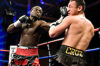 Brooklyn, NY - 04.03.2008: Joshua Clottey (red/black trunks) lands on  Jose Luis Cruz during their 10 rounds super welterweight fight at the Aviator Sports & Recreational Center. IBF #1 Clottey won by tko in the fifth round. Photo by Thierry Gourjon