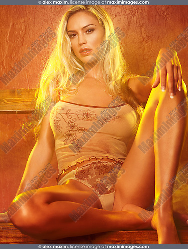 Sensual portrait of a glamorous young woman sitting on a bench in steam room
