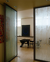 Large double doors of etched glass open into the kitchen/dining area from the entrance hall of an Amsterdam apartment converted from an old tramshed