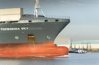 The prow of the container ship, Pomerania Sky is exposed as she steams downriver on the River Thames.