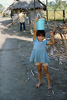 Shipibo Indian girl carrying water in village on shores of Ucayali River, Peru. Shipibo language belongs to the Panoan family.