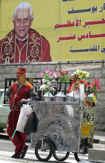 A drinks vendor serves customers next to a banner welcoming Pope Benedict XVI in the West Bank city of Bethlehem, on May 10, 2009, three days before the historic visit of the Pope. Pope Benedict XVI is on a week-long tour in the Middle East that includes Jordan, Israel, and the Palestinian territories. APAimages Photo / Najeh Hashlamoun