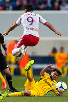 Fabian Espindola (9) of the New York Red Bulls jumps over Matías Sanchez (8) of the Columbus Crew. The New York Red Bulls and the Columbus Crew played to a 2-2 tie during a Major League Soccer (MLS) match at Red Bull Arena in Harrison, NJ, on May 26, 2013.