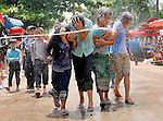 Girls are being shot with water during the Lao New Year (Pi Mai) celebrations when throwing or shooting water  over people is a way to wash away the old years spirits in Luang Prabang, Laos.