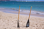 Two canoe paddles left in sand on Kailua beach on a sunny morning. Kaneohe Marine Base is in the background.