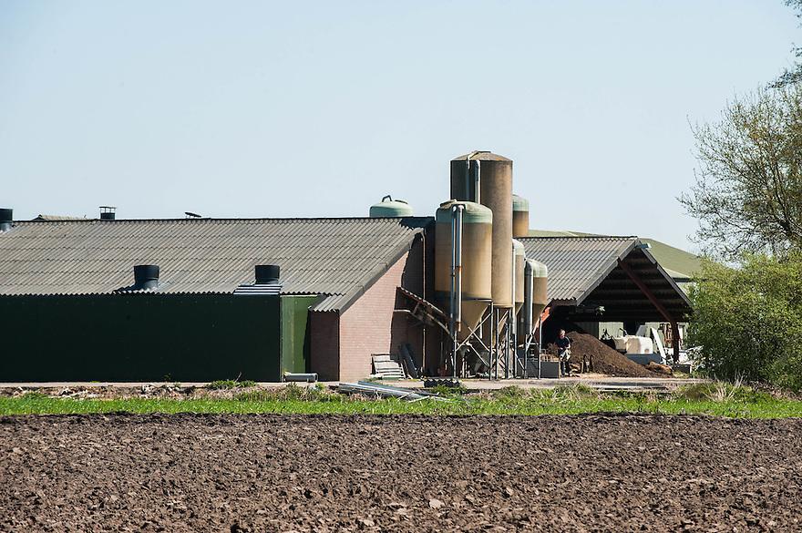 Nederland, omgev. Veghel, 20 april 2015<br /> Grote stallen en voedersilo's in het brabantse landschap. <br /> <br /> Foto: Michiel Wijnbergh