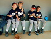 A little league teams watches as their friends play. Erik Kellar