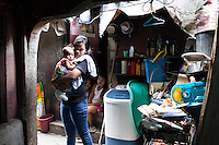 Single mother Josephine Savares, 18, holds her 1st child Jihan, aged 4 months, outside her family house where she lives with her father, in Paranaque, Metro Manila, The Philippines on 19 January 2013. Josephine had decided to feed her baby formula during her pregnancy and had no idea that her father had to pay such a high price for it. Her family goes without food some days, and her siblings have had to stop school in order to afford the formula. Photo by Suzanne Lee for Save the Children UK