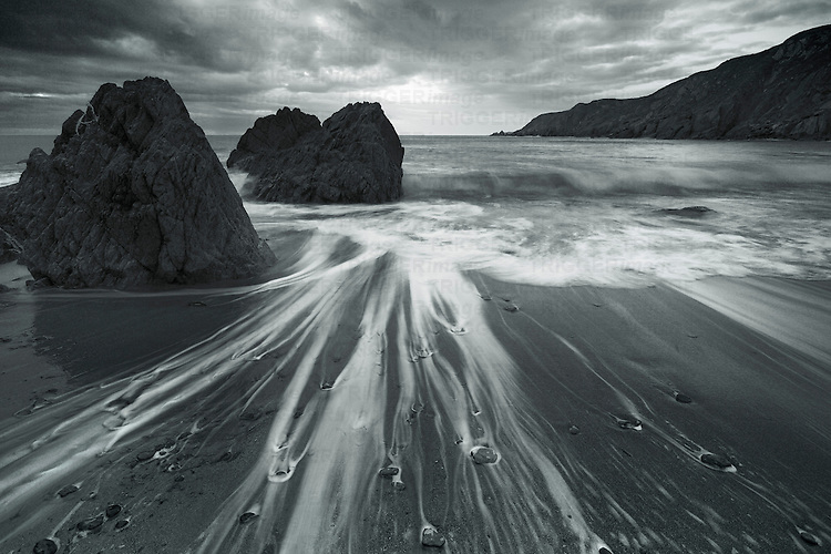 Sea water moving over sand and around rocks on a beach