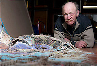 BNPS.co.uk (01202 558833).Pic: RachelAdams/BNPS..Picking up the pieces.....A jigsaw creator who spent over a month making a 40,000 piece puzzle for a world record attempt has had to start again - as it collapsed just one day after he finished...Craftsman Dave Evans from Weymouth in Dorset was hoping to create the largest hand-cut wooden jigsaw and spent 35 days making it out of 33 images of the Queen's Diamond Jubilee...Just one day after he put in the final segment of the 19ft 6in by 8ft masterpiece, Dave noticed it had moved slightly due to the sloping floor, and tried to adjust it...But as he moved the enormous puzzle he became distracted by someone asking for directions, and it suddenly collapsed from the frame and crumpled to the floor...Luckily Dave had already measured, photographed, and filmed the world record bid and sent the information off to the Guiness World Records before it was destroyed..