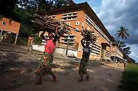 Women carry firewood along the riverfront in Yangambi, DR Congo, on Tuesday, Dec. 9, 2008.  The largest building in Yangambi faces the riverfront and was perviously a maintenance centre and repair garage for the entire facility. It now lies abandoned and derelict. .Yangambi Research Station is the former Belgian headquarters for all major scientific ecological, biological and agricultural research in Africa between the 1930's and 1960. It stretches for 33 km inland from the river and contains 250 residential houses and many research buildings and offices, including a herbarium and library. At it's height approximately 250 scientists and 500 technicians were based here along with 1000 more Belgian workers ranging from doctors to bricklayers. With the families and constant visitors to the station included the total population of would have ranged in the several thousands. Abandonment began in 1960 with independence and although Congolese attempted to maintain Yangambi, sometimes in co-operation with the Belgians, the facility began to fall into disrepair through the 70's and 80's. War in the 1990's halted all potential for progress and for the past decade a skeleton crew has made a futile attempt to stave off further decline.