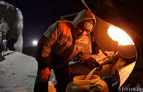 A man working for the oil and gas prospecting company &quot;Bashneft&quot; collects hot water in the Arctic tundra. <br /> The water is cooked with diesel. <br /> Typically, these men work in the cold, isolated wilderness for the entire winter, returning to civilisation only in spring.
