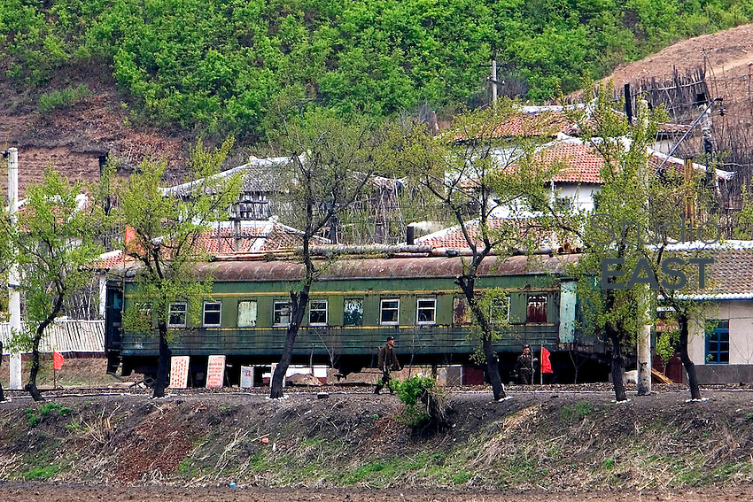 North Korean soldiers carrying rifles walk by a disused train wagon, as seen from a location near Kaishantun, Jilin province, China, on May 10, 2009. When one looks at North Korea from China, North Korean soldiers are always seen around, carrying rifles. Photo by Lucas Schifres/Pictobank