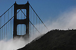 The fog rushes up a hillside framing the Golden Gate Bridge.